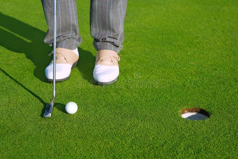 Golf al hombre verde del curso del agujero que pone la bola corta imagenes de archivo