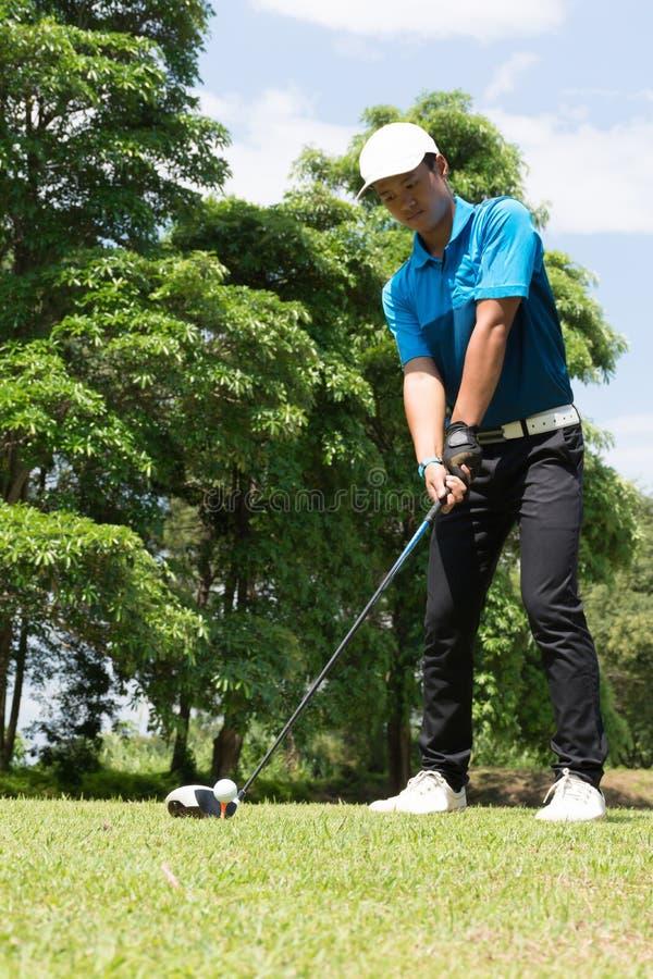 Golf asiatico bello di tiro in buca dell'uomo del giocatore di golf fotografia stock libera da diritti
