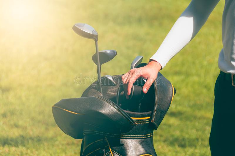 Golf athletes are choosing golf clubs royalty free stock image