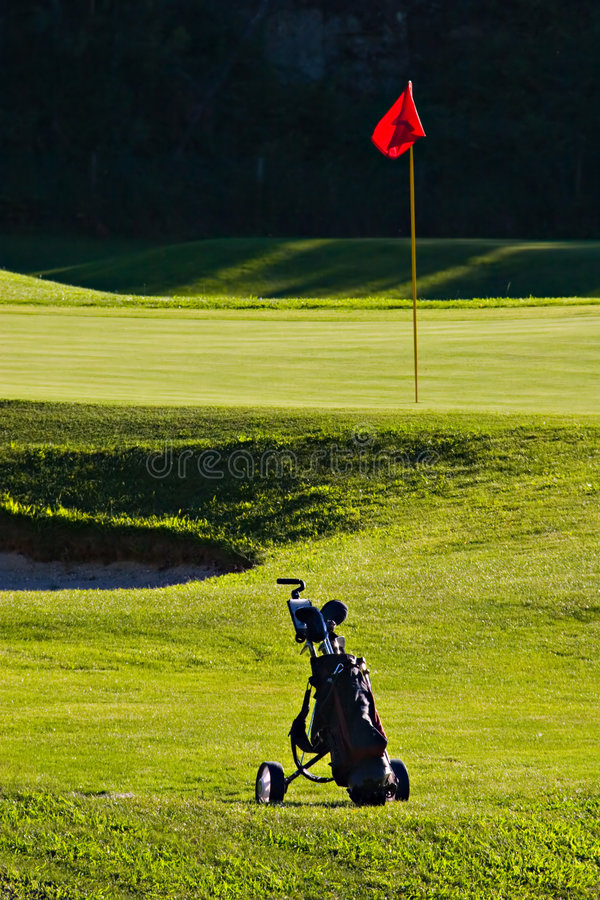 Golf bag. Near golf green, with pole and red flag