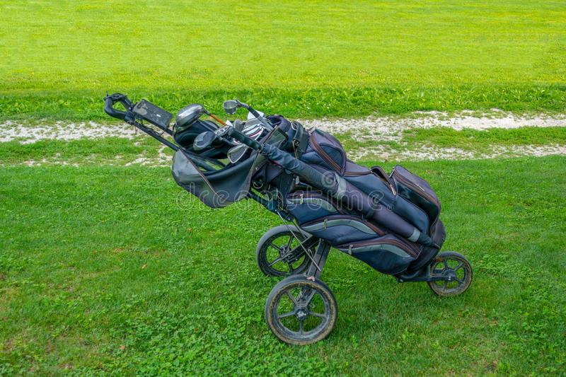 Golf bag with clubs on roller stand on golf course royalty free stock images