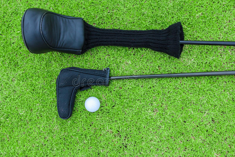Golf bags and golf ball on a tee in green grass course royalty free stock images