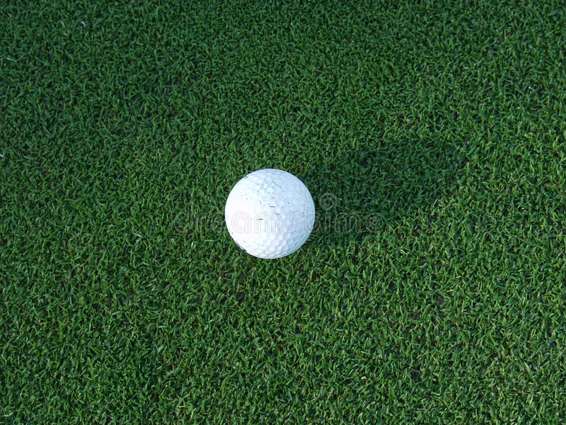 Golf Ball. Residing on a perfectly cut Green royalty free stock photos