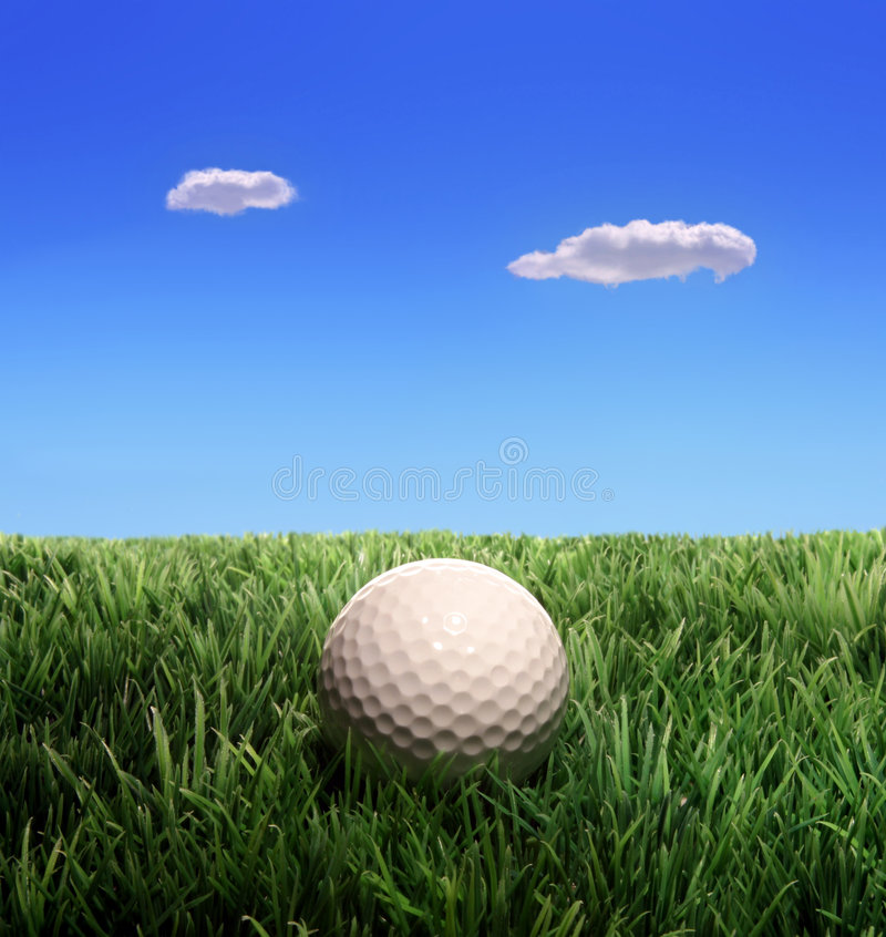 Golf Ball. On plastic grass against blue sky and clouds royalty free stock photography