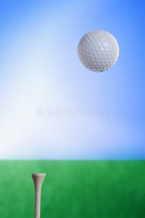Golf Ball in Air. A golf ball flying through the air. A tee is stuck in the ground and grass and sky fill the background stock photography