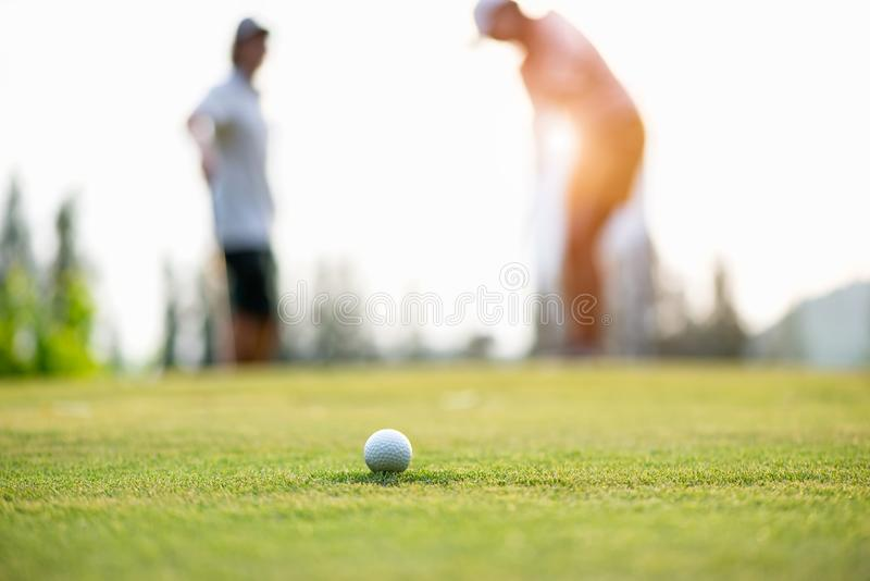 Golf ball approach to the hold on the green. Couple golf player putting golf ball in the background. Lifestyle Concept royalty free stock photos