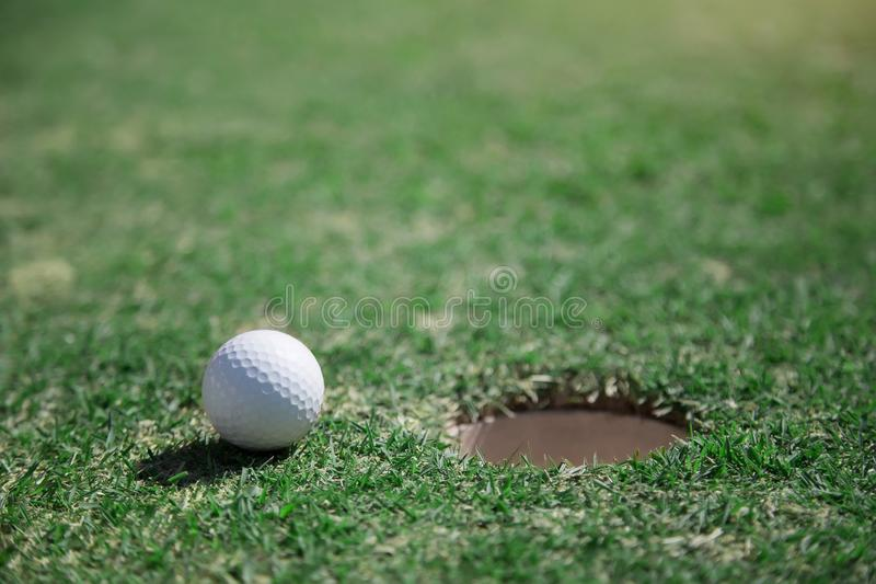 Golf ball close hole on green grass field. close to goal target concept with golf sport caption. Golf ball close to hole on green grass field. close to goal royalty free stock image