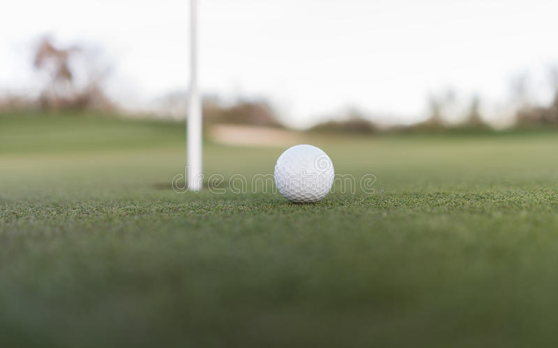Golf ball close to cup hole on putting green stock photography