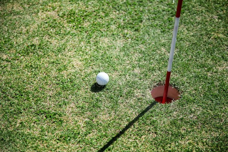 Golf ball close to hole on green grass field. close to goal target concept with golf sport caption. Golf ball close to hole on green grass field. close to goal royalty free stock image