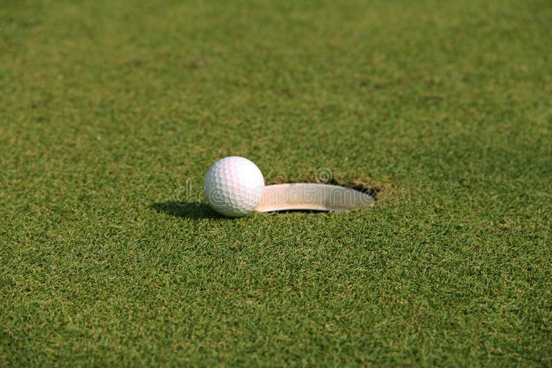 Golf ball close up on green in golf coures at Thailand. Golf ball close up on green in grass field with sunset. Golf ball close up in golf coures at Thailand royalty free stock image