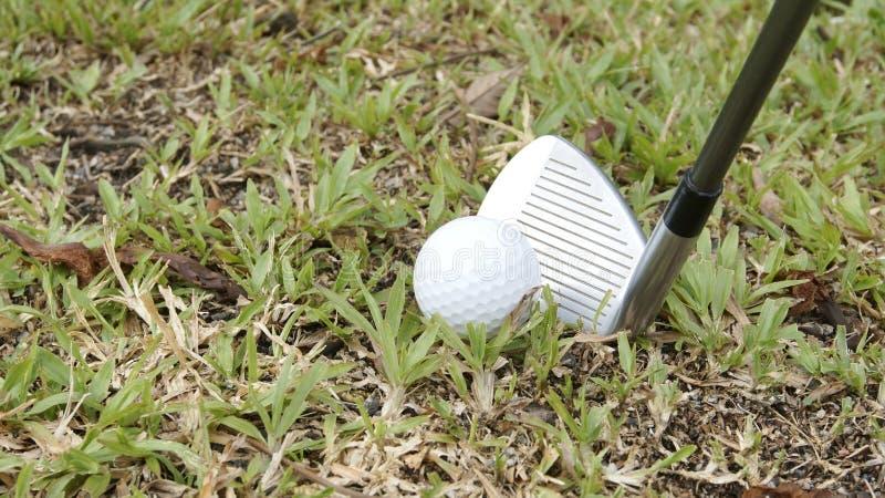 Golf ball and golf club ready for swing. Golf ball and golf hybrid club ready for swing. Golf ball and golf hybrid club ready for stock image