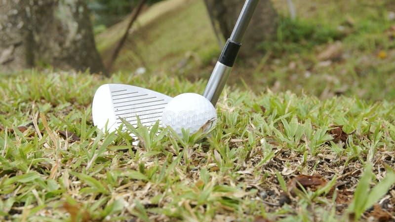 Golf ball and golf club ready for swing. Golf ball and golf hybrid club ready for swing. Golf ball and golf hybrid club ready for royalty free stock photos