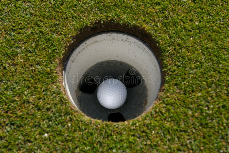 Golf ball in the cup royalty free stock photos