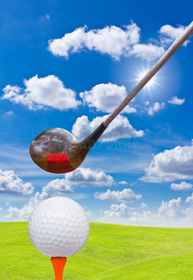 Golf ball and driver on green grass. And blue sky stock image