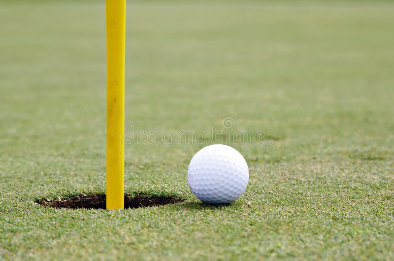 Golf ball on the edge of the c stock photography