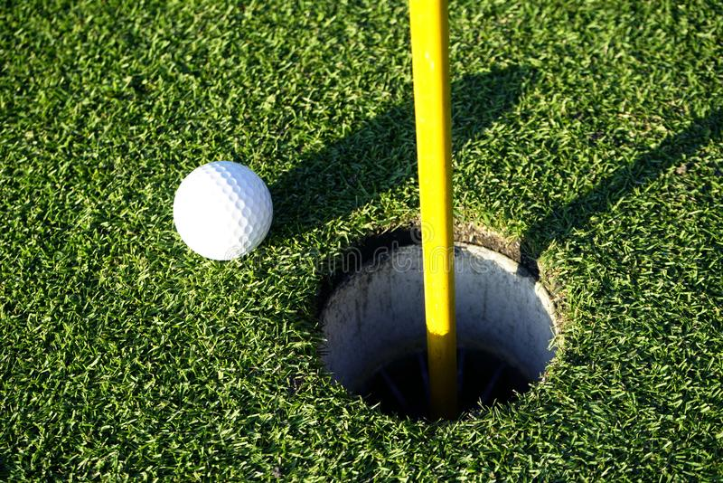 Golf ball on the edge of hole on the green grass. Golf ball on the edge of hole on putting green on golf course stock photos