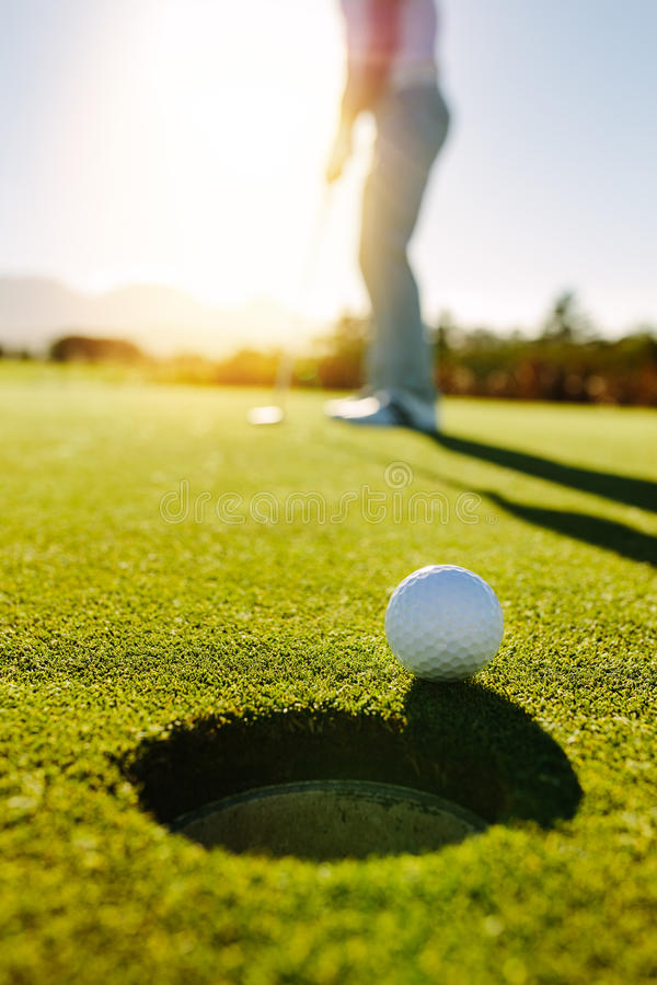 Golf ball at the edge of hole with player in background. Professional golfer putting ball into the hole on a sunny day royalty free stock photos
