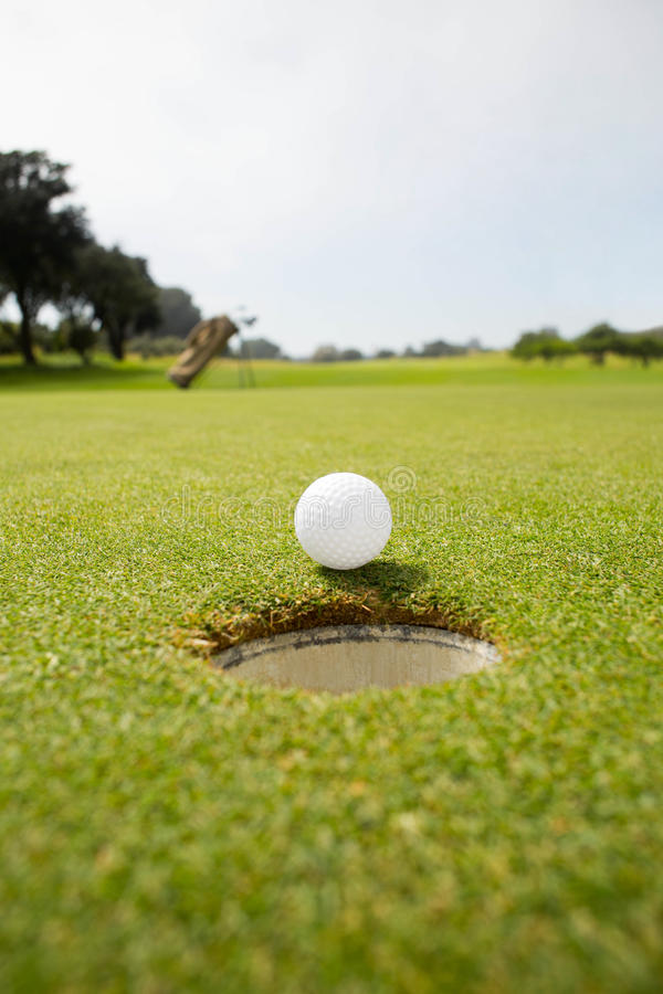 Golf ball at the edge of the hole royalty free stock image