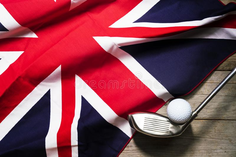 Golf ball with flag of UK on wood table royalty free stock photo