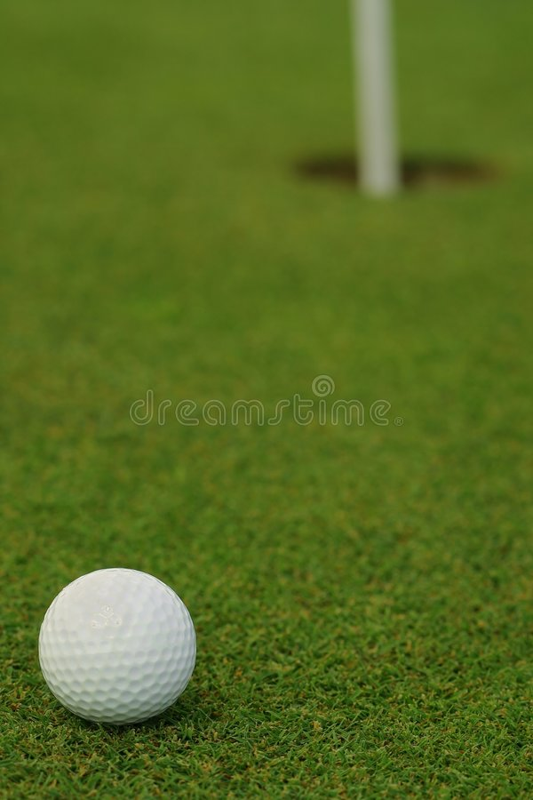 Golf ball in front of the hole royalty free stock photography