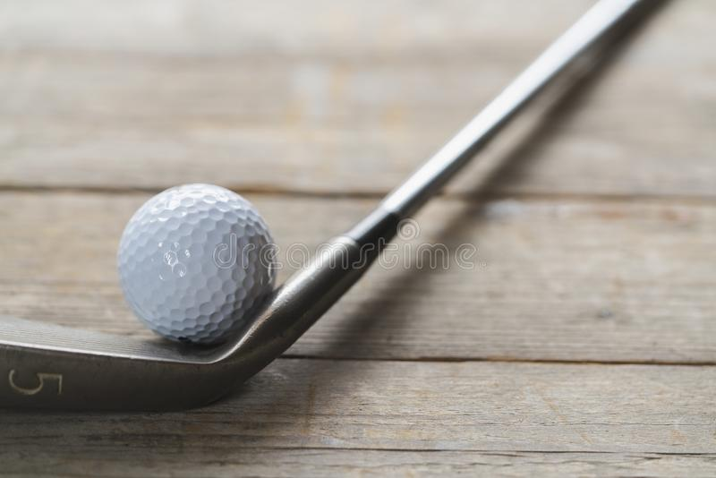 Golf ball and golf club on the table background royalty free stock image