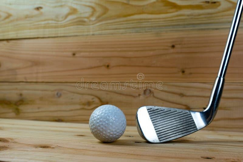 Golf ball and golf club on wood floor stock photo