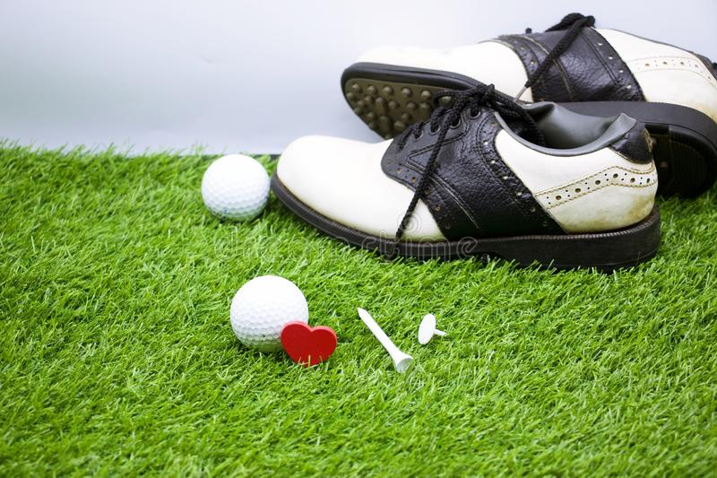 Golf ball and shoes are on green grass stock photos