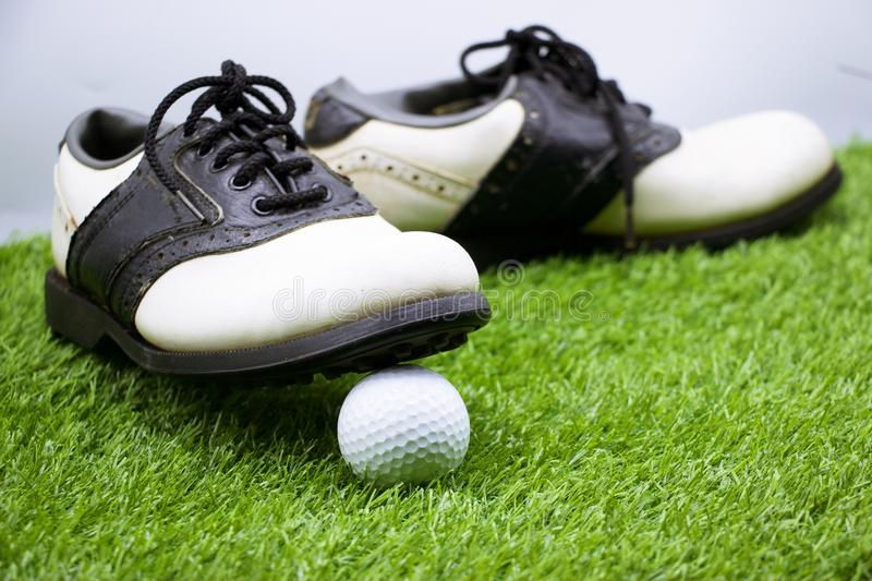 Golf ball is on green grass with golf shoes royalty free stock photography