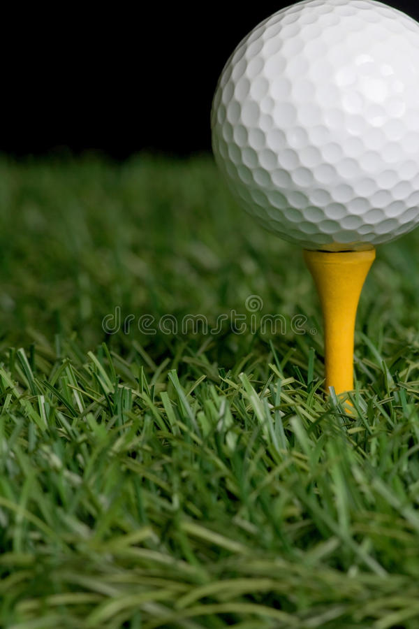 Golf ball. On grass with black background stock photography