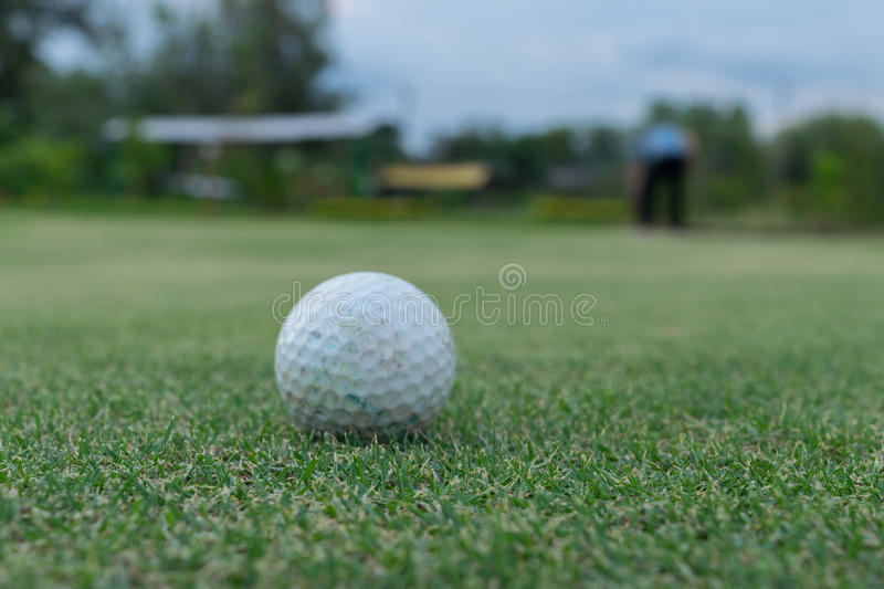 Golf ball on green and Golf player stock photo