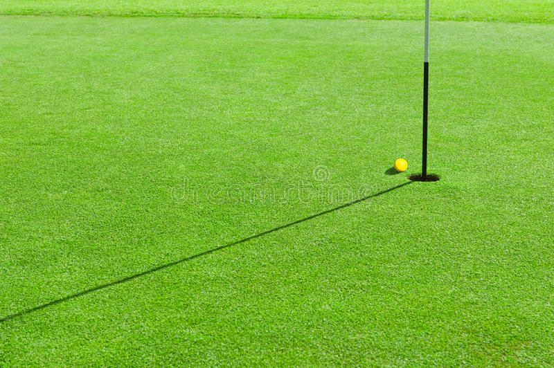Golf ball on the green grass. Golf ball on the edge of hole on the green grass stock images