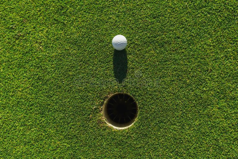 Golf ball on green grass with hole and sunlight. Lawn, object, cut, putting, equipment, playing, landscape, empty, point, natural, ground, lifestyle, shot royalty free stock images