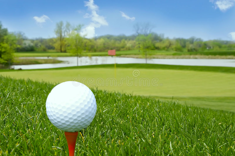 Golf ball on the ground. Goal ball on red tee with beautiful golf course in the background stock photos