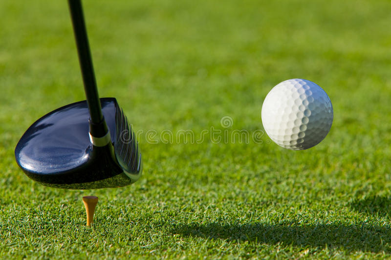 Golf ball hit off the tee with driver on golf cour royalty free stock images