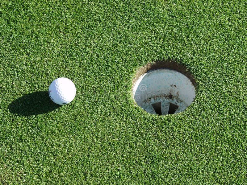 Golf ball and hole. Golf ball that has come to rest next to a hole on a green royalty free stock images