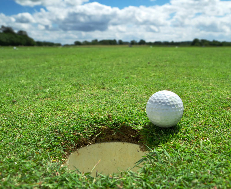 Golf ball at the hole royalty free stock images