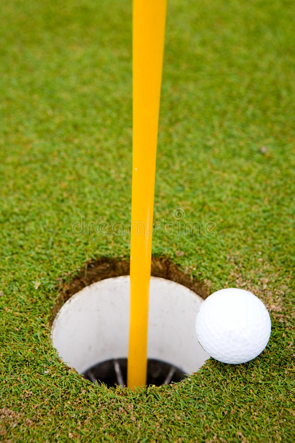 Golf Ball Hole. Golf ball very close to going in the hole stock images