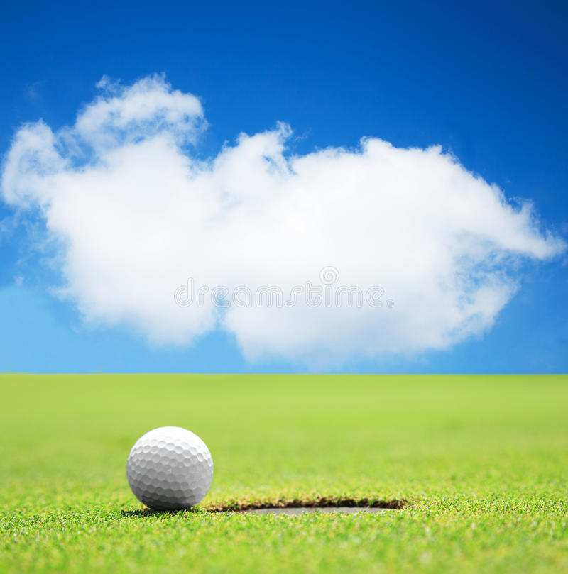 Golf ball at the hole with beautiful sky royalty free stock photography