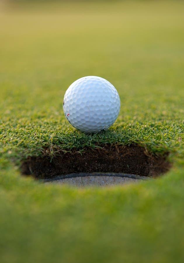 Golf ball by the hole stock photos