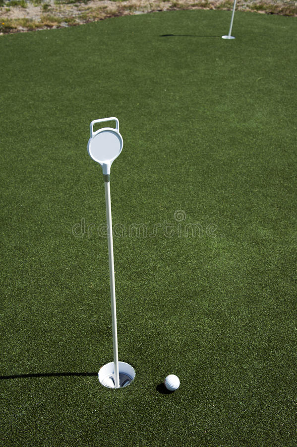 Golf ball and hole on a field