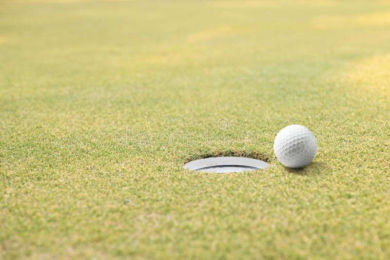 Golf ball and golf hole on green grass with copy space stock photo