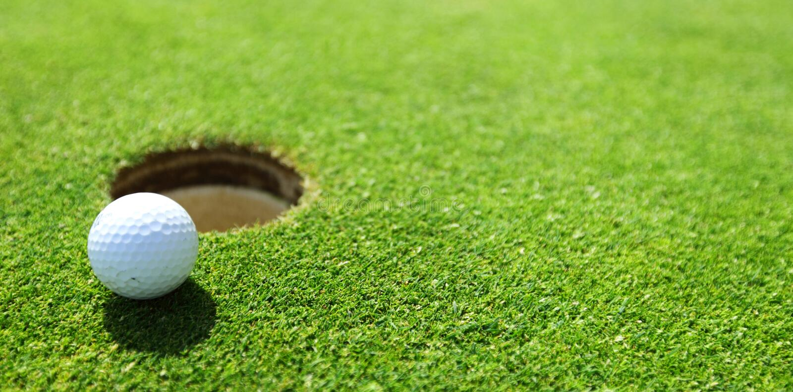 Golf ball on lip of cup. Close up stock photo
