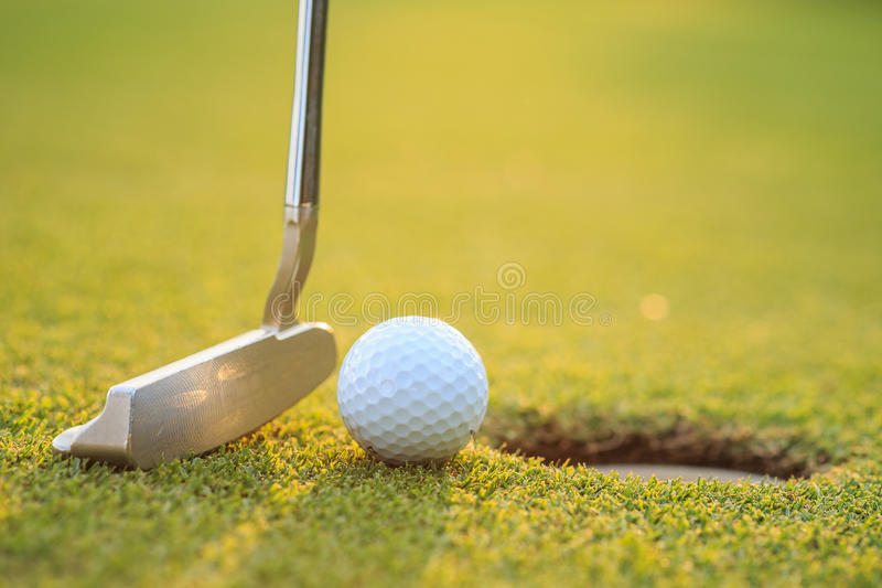 Golf ball on lip of cup in course stock photography