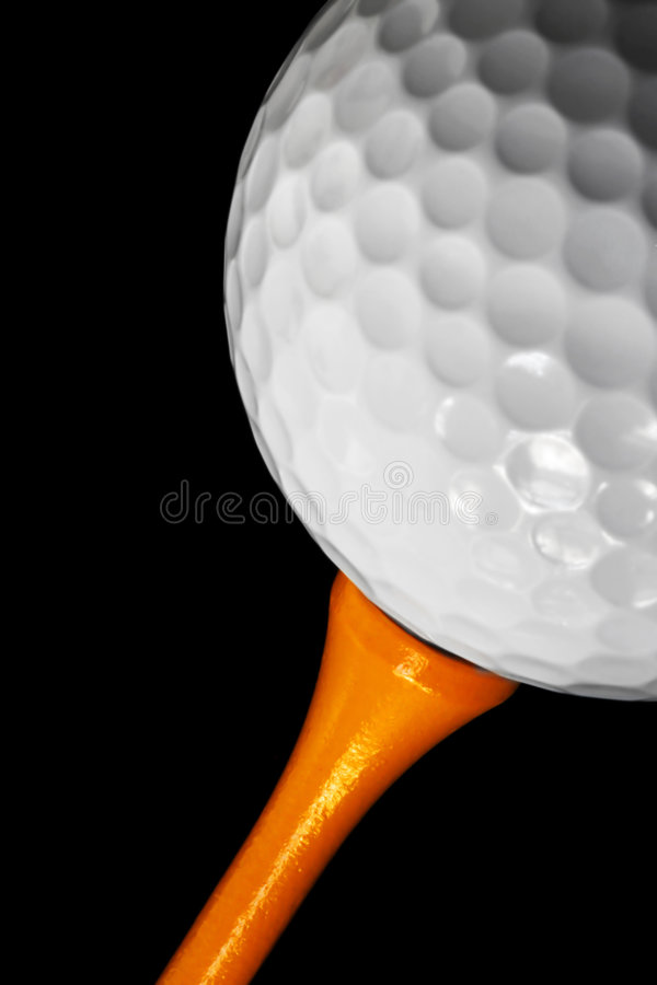 Golf Ball Macro. Macro of a golf ball on a tee, with black background stock photo