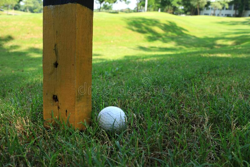 Golf Ball beside Marker Pole. It is an immovable obstruction as stated in Golf Rule 24 stock photo