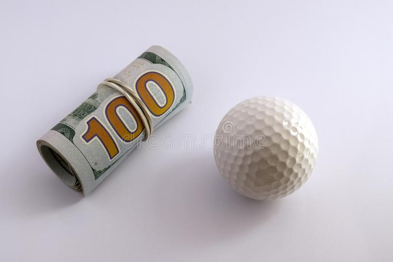 Golf ball next to a roll of hundred dollar bills of the USA with a white rubber band. The concept of sports betting, golfing. Golf ball next to a roll of hundred stock photo