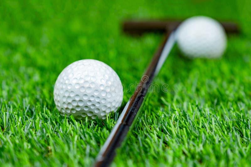 Golf ball and putter on grass stock photos