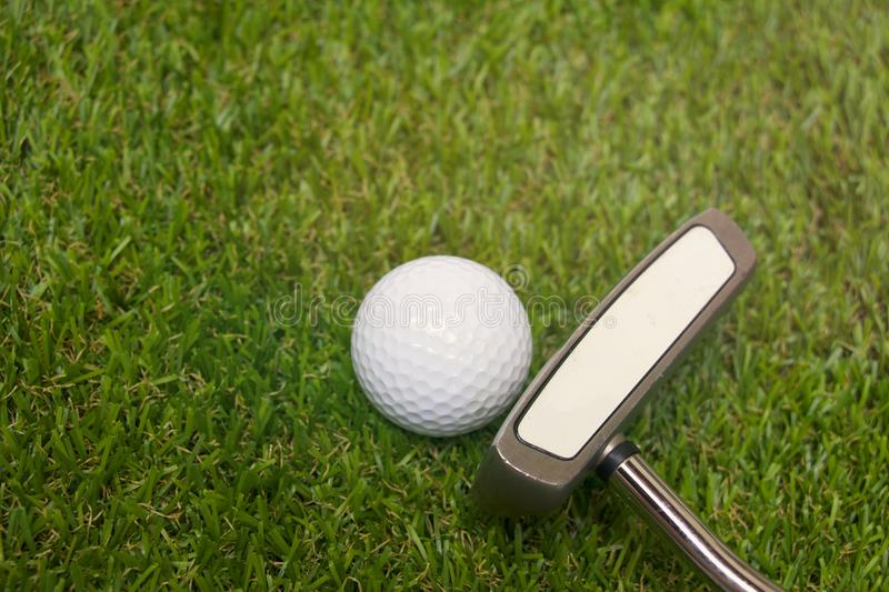 Golf ball and putter on green course stock photo