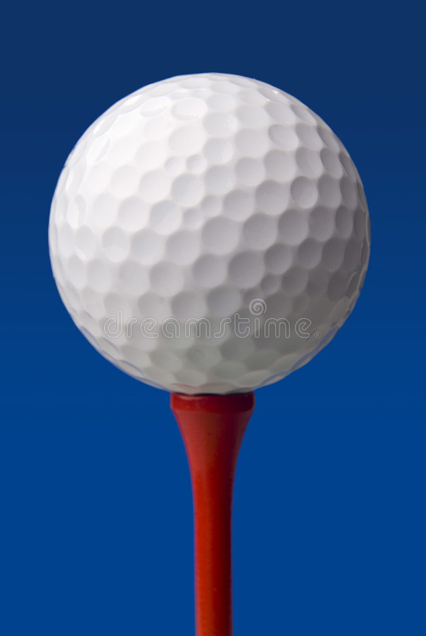 Golf ball on red tee, blue background stock photos