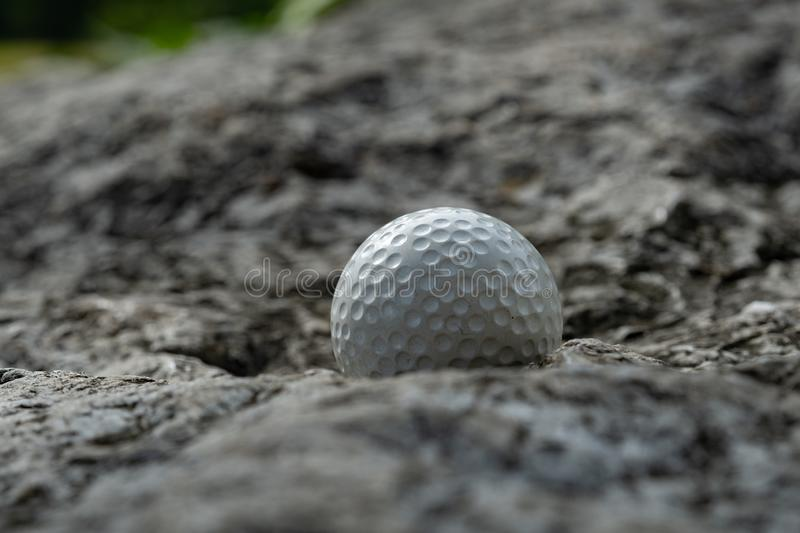 Golf ball on rock stock images